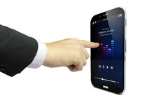 Touching a smartphone with music app on the screen. Businessman hand touching a smartphone with music app on the screen Royalty Free Stock Image
