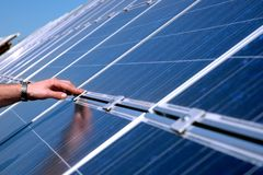Touching a solar panel. Renewable energy source royalty free stock photos