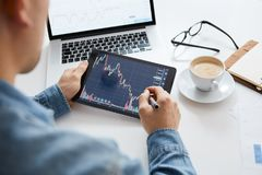 Touching stock market graph on a touch screen device. Trading on stock market concept stock images