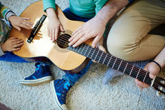 Touching strings of guitar Stock Photos