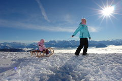 Touching the sun. Mother pulling her child on the sledge at high quotes, almost touching the sun Royalty Free Stock Image