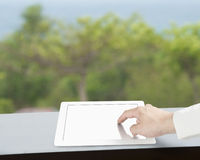 Touching tablet with blank screen. On table Royalty Free Stock Photography