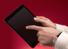 Touching a tablet on red. A man touching a tablet with his finger with a red faded background. Place you own graphics stock photos