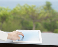 Touching tablet on table with green background. Touching tablet on table with green view outdoor Royalty Free Stock Photos