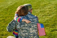Touching US army soldier reunion with little daughter. A young child is hugging his army soldier father and holding a usa flag stock photography