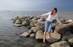 Touching the water. Girl on a beach Royalty Free Stock Photo