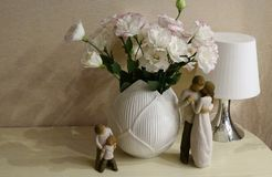 Touching Wooden figures of parents and children near a bouquet of flowers. The image in pastel tones. stock photo
