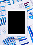 Touchpad above financial paper charts and graphs Royalty Free Stock Photography