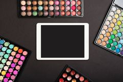 Touchpad with blank screen with colorful eyeshadow palettes on black background. Flat lay. Of tablet computer with makeup palettes stock photo