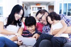 Touchpad för kvalitets- tid för familj hemmastadd användande Fotografering för Bildbyråer