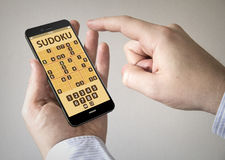 Touchscreen smartphone met de toepassing van het sudokuspel op scre Stock Afbeeldingen