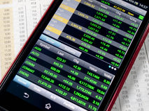 Stock market. Touchscreen smartphone with stock market application Stock Image