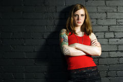 Tough. A young female with full arm tattoo leaning up against a black brick wall Stock Photos