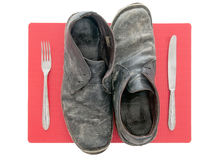 Tough as old boots. Indigestion, poor quality meat concept. Unbranded worn old leather boots on red place setting. Isolated on white Royalty Free Stock Photography