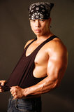 Tough asian guy 2. Tough Asian guy in a black tank top which he is tugging on Royalty Free Stock Photography