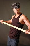 Tough asian guy. In a black tank top holding a stick Royalty Free Stock Photo