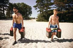 Tough athletes doing workout on beach with jerrycans Stock Photo