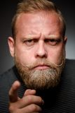 Tough bearded guy. Portrait of tough bearded guy on black background. Short-haired blond man having a bone to pick with someone Royalty Free Stock Photography