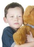 Tough boy cuddling bear Royalty Free Stock Photos