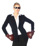 Tough business woman. Young, blond female dressed in a business suit with boxing gloves and sunglasses against a white backdrop Royalty Free Stock Image