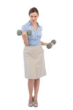 Tough businesswoman lifting dumbbells looking at camera Stock Photo