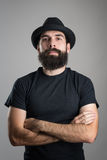 Tough confident bearded hipster with crossed arms wearing black t-shirt and hat looking at camera Stock Photos
