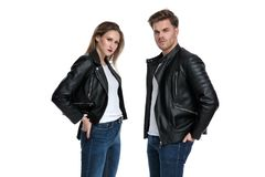 Tough couple standing with their hands in their back pockets. And looking to the camera while wearing leather jackets and jeans on white studio background stock photography