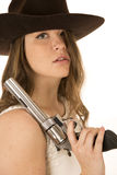 Tough cowgirl holding large pistol hair in face glaring. Tough cowgirl holding large pistol glaring at the camera royalty free stock images