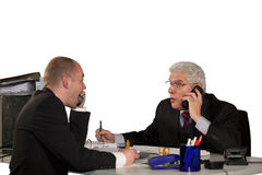 Tough discussion during telephone conference. Two businessmen having a tough discussion during a telephone conference Stock Photo