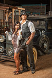 Tough Gangster with Cute Woman. Handsome muscular 1920s gangster with lady in mini skirt Royalty Free Stock Images