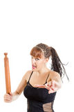 Tough girl in black dress threatening with rolling pin Stock Photo