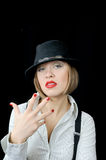Tough girl in hat shows fingers Royalty Free Stock Photography