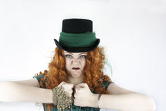 Tough girl wearing top hat. Beautiful young woman with long, curly red hair wearing top hat making a tough, mean face royalty free stock photography