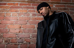 Tough guy. Dressed in black near a brick wall Stock Image