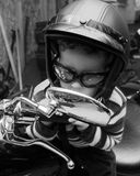 Tough Guy. Little boy on a motorcycle in a garage with dad's helmet and glasses, in black and white Stock Images