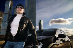 Tough guy. In leather jacket near his car and skyscrapers at background Stock Photography