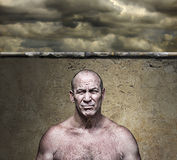Tough Guy Against a Wall. Scary big mean man scowling under a threatening sky Royalty Free Stock Images
