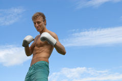 Tough guy in boxing gloves. Tough angry guy in boxing gloves, on blue sky background stock photography