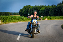 Tough guy on chopper bike in motion on the road Royalty Free Stock Photos