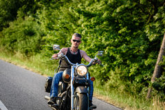 Tough guy on chopper bike in motion on the road Royalty Free Stock Photography