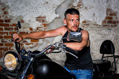 Tough guy with his bike in front of a brick wall Royalty Free Stock Photography