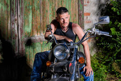 Tough guy with his bike in front of a green barn door Royalty Free Stock Photos