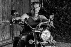 Tough guy with his bike in front of a green barn door. Tough guy with sparrow beard, undercut and blue jeans sitting on a chopper bike in front of  a green Stock Images