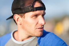 Tough guy portrait. Man in a trucker cap. Outdoor shoot Royalty Free Stock Image