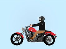 Tough guy riding a motorcycle. Tough brutal men wearing black helmet with spikes on a red chopper Stock Photo