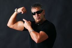 Tough guy showing off. Tough guy with dark glasses, could be criminal, showing his big bicep muscle has an intimidation tactik, studio shot over black Stock Photo