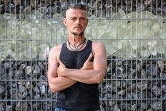 Tough guy standing thoughtful in front of a wall of stones Royalty Free Stock Photo