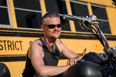 Tough guy with sun glasses lolling on his chopper motorcycle. Tough guy with sparrow beard, undercut, black rip shirt and sun glasses lolling on his chopper Royalty Free Stock Photos