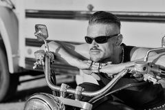 Tough guy with sun glasses lolling on his chopper motorcycle. Stock Photos