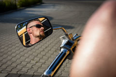 Tough guy with undercut reflecting in the mirror of his bike Stock Photo